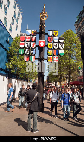 A tourist looking at the emblems of all the Swiss cantons, Swiss Court, The Swiss Centre, Leicester Square, London, - Stock Photo
