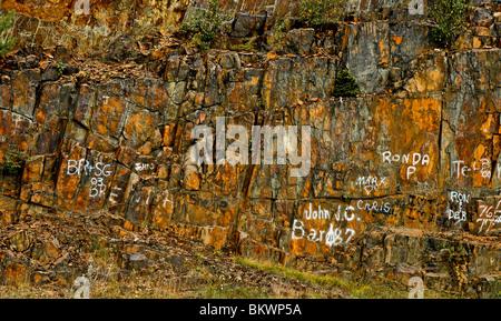 Stock photograph of graffiti on a rocky cliff along the highway near Bucksport Maine USA