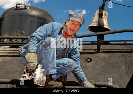 Stock photo of engineer cleaning coal cinders off locomotive,Durango and Silverton Narrow Gauge Railroad,Silverton,Colorado,USA. - Stock Photo