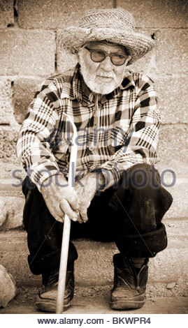 Greek old man wearing straw hat and sunglasses sitting in a village Greece - Stock Photo