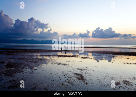 Two people walk along the shore while the tide is out at sunset - Stock Photo