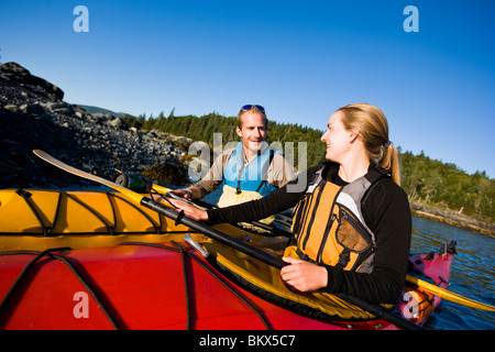 A young couple sea kayaking near the Porcupine Islands in Maine's Acadia National Park.  Frenchman Bay.  Bar Harbor. - Stock Photo