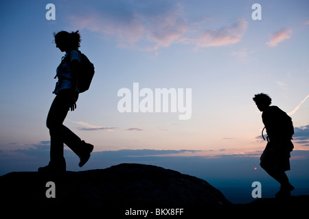 A couple hikes at sunset on the summit of Mount Monadnock in Monadnock State Park in Jaffrey, New Hampshire. - Stock Photo