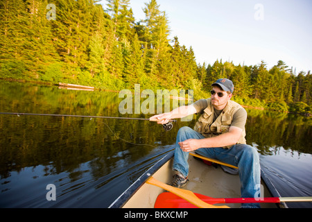 A man fly-fishing from a canoe on Little Greenough Pond in Errol, New Hampshire. - Stock Photo