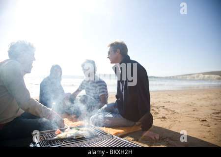 Group of friends sitting around a barbeque on the beach