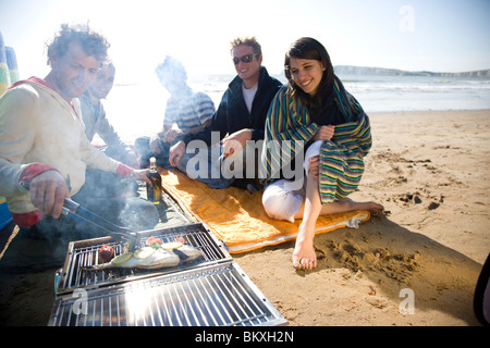 Group of friends sitting around a barbeque on the beach - Stock Photo