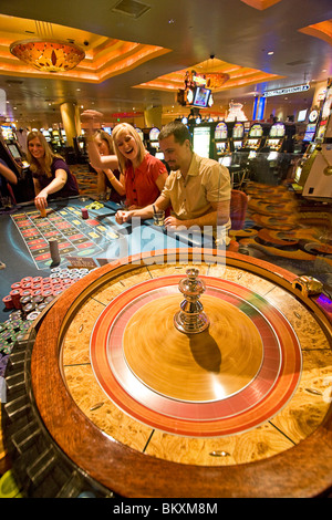 Scene on gaming floor of casino - excited players bet as roulette wheel spins, South Lake Tahoe, Nevada, USA. - Stock Photo