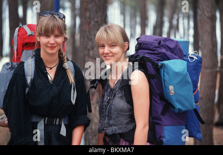 Teenage backpacker holiday, two female backpackers happy look at camera. - Stock Photo