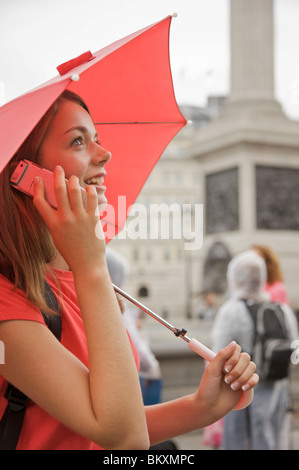 Teenaged girl holding a red umbrella and talking on a cell phone in London Trafalgar Square - Stock Photo