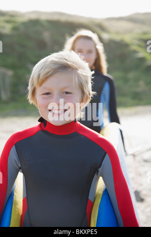 Close up of a smiling boy in a wetsuit carrying a surfboard with a girl - Stock Photo