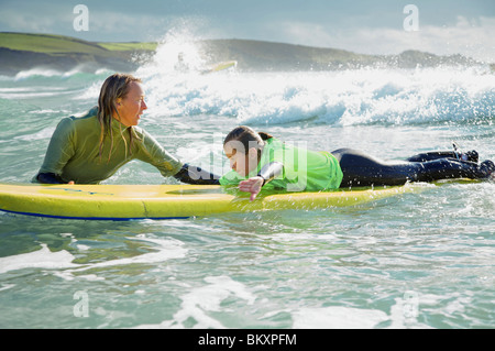 Woman in the sea holding a surfboard with a girl lying on it - Stock Photo