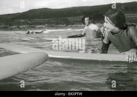 Girl in the sea holding on to her surfboard with surfer behind her - Stock Photo