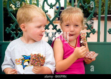 A young brother and sister enjoy Balboa Bars, a traditional and tasty ice cream treat on Balboa Island in Newport - Stock Photo