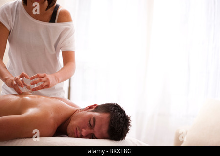 Man receiving cupping therapy on his back - Stock Photo