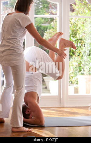 Yoga instructor helping man in the head-stand position - Stock Photo