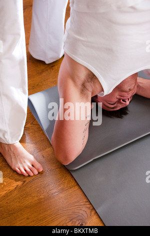 Yoga instructor helping man in the head-stand position - close up - Stock Photo