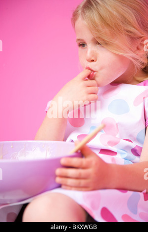 Close up of a young girl holding a baking bowl sucking her finger