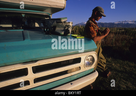 A man ties a fly next to his truck while fly fishing in Bishop, California. - Stock Photo