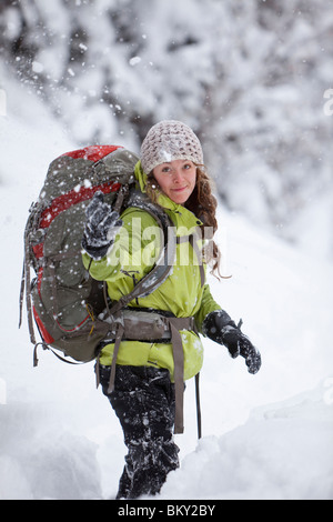 A young woman throws snow in the air while hiking in fresh powder in the Wasatch Mountains, Utah. - Stock Photo
