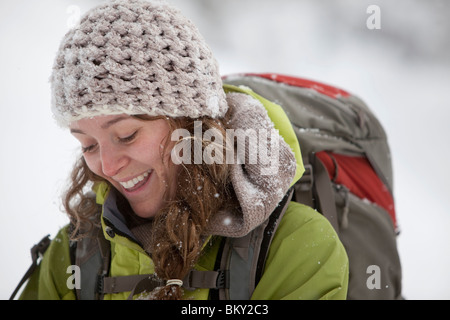 A young woman hikes with a backpack in fresh powder in the Wasatch Mountains, Utah. - Stock Photo