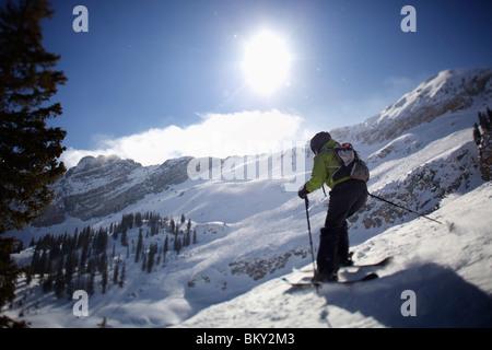 A woman skis in Utah under bright, blue skies. - Stock Photo