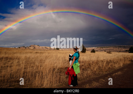 Mother and newborn baby with a rainbow over the grass, hills and trees of Blue Mountain, Missoula, Montana - Stock Photo