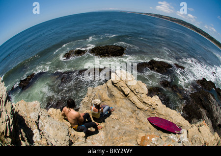 A young man and woman sitting on a rocky point while watching surfers at Punta de Lobos, Puchilemu, Chile. (fisheye) - Stock Photo
