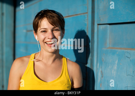 Woman in her late 20's wearing her workout clothes and headphones looks at the camera and smiles in San Diego, California. - Stock Photo