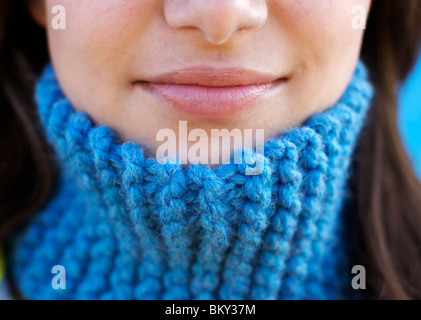 Close-up shot of a young female's smiling lips wearing a blue wool scarf around her neck. - Stock Photo