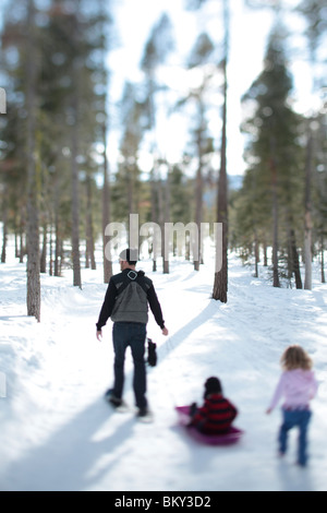 A father snowshoe with an infant and a toddler in the snow covered wilderness of Lake Tahoe, Calfornia. - Stock Photo
