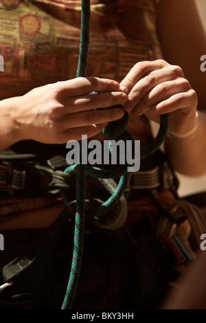 A female rock climber ties into her climbing rope at Red Rock Canyon. - Stock Photo