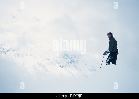 Skier taking in the view on massive slopes high above Chamonix Valley. - Stock Photo