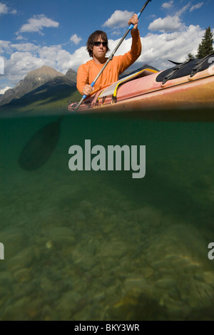 Solo paddler sea kayaking on a remote lake in Glacier National Park. - Stock Photo