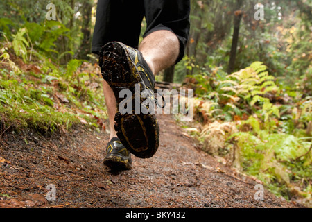 The feet of a man trail running along a wet muddy trail in the Olympic National Park.