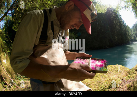 A man picks a fly from his fly box while  fishing in Squamish, British Columbia. - Stock Photo