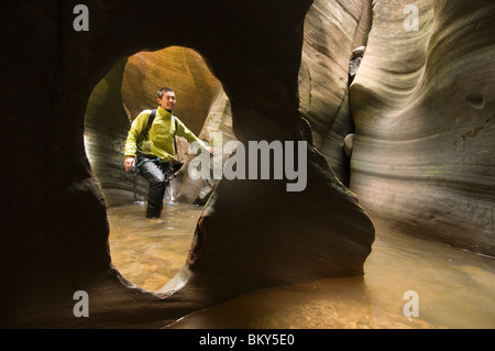 An Asian man canyoneering through a watery canyon in Zion National Park, Springdale, Utah. - Stock Photo