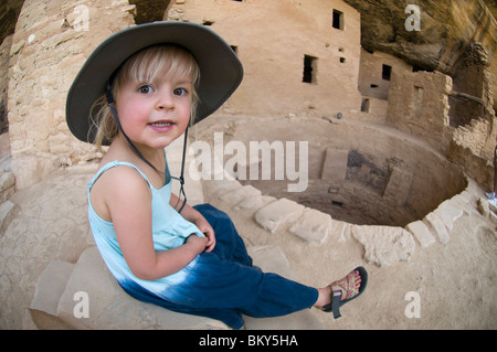 A young girl rests on a stone wall while exploring ruins in Mesa Verde National Park, Cortez, Colorado. - Stock Photo