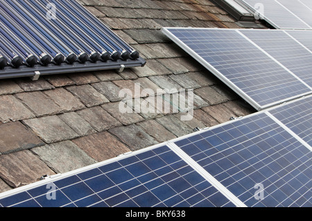 Solar voltaic electricity generating panels and solar hot water panels on a house roof in Ambleside, Cumbria, UK. - Stock Photo