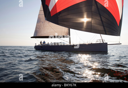A crew races a modern ocean-going sailing yacht under spinnaker. - Stock Photo