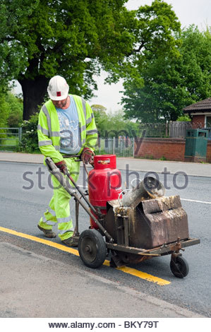 Man painting a single yellow line on the road, UK. Workman using hand operated machine marking out road with hot - Stock Photo