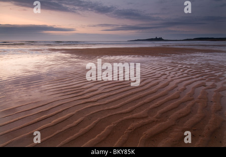Ripples in the sand with Dunstanburgh Castle in the distance at Dawn - Stock Photo