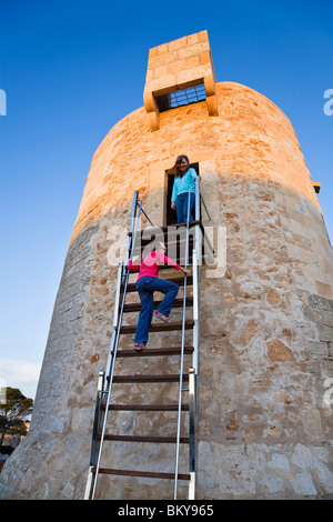 Two girls on the ancient watchtower in the evening light, Cala Santanyi, Mallorca, Balearic Islands, Mediterranean - Stock Photo