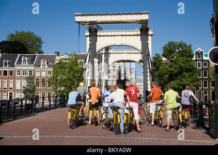 Cyclists, Magere Brug, Group of cyclists on Magere Brug Skinny Bridge, over Amstel, rear view, Amsterdam, Holland, - Stock Photo
