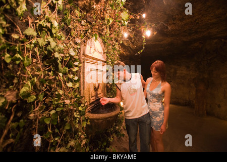 Couple near wine fountain in Buda Castle Labyrinth, Couple next to the wine fountain in Buda Castle Labyrinth, Buda, - Stock Photo