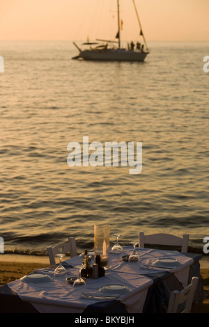 View over a table with glasses and plates to a sailingboat on the sea, Little Venice, Mykonos-Town, Mykonos, Greece - Stock Photo
