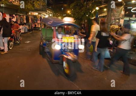 Tuk Tuk passing Th Khao San Road in the evening, Banglamphu, Bangkok, Thailand - Stock Photo