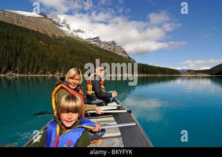 Family in paddle boat, Moraine Lake, Banff National Park, Alberta, Canada - Stock Photo