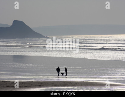 Parents and child enjoying a winter walk along Newgale beach in Pembrokeshire, South Wales. - Stock Photo