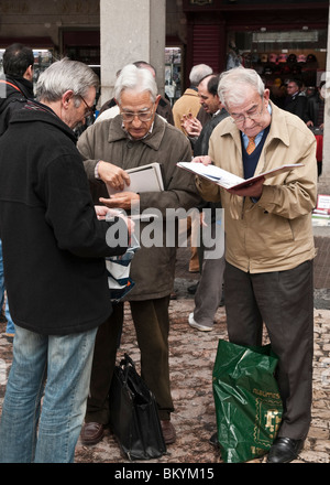 Philatelists, stamp collectors, at the Sunday stamp and coin collectors market in The Plaza Mayor, central Madrid, - Stock Photo