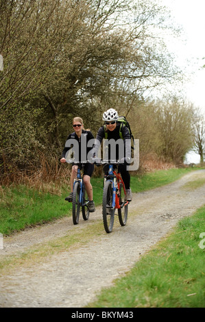 Two young women cycling on the Ystwyth Trail, near Tregaron CVeredigion Wales UK - Stock Photo